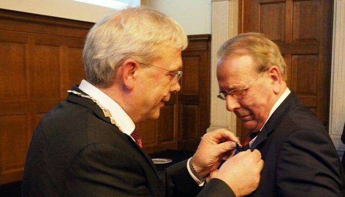 Burgemeester Koos Wiersma reikt de onderscheiding uit aan Jeff de Hosson